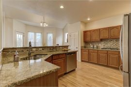 marble counters and wooden cabinets in a large kitchen