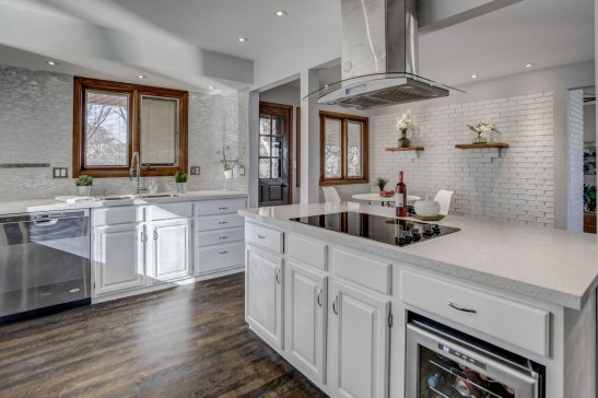 A white island with white cabinets and white tiled wall in this Colorado kitchen